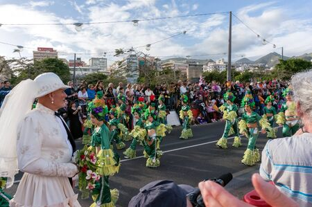 A man in a double suit of the bride and groom stands on the background of the carnival procession. Santa Cruz de Tenerife. Spain