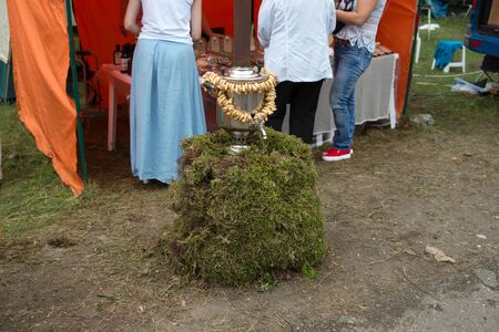 The samovar, with bunches of bagels and poppy seeds, stands on a moss stand, in front of a shopping tent with people.