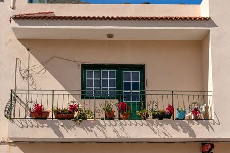 Balcony on an old whitewashed building, decorated with flowers in pots in the Spanish city