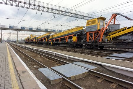 Freight train with industrial equipment stands on the tracks of a junction railway station with rails in the foreground. Reklamní fotografie