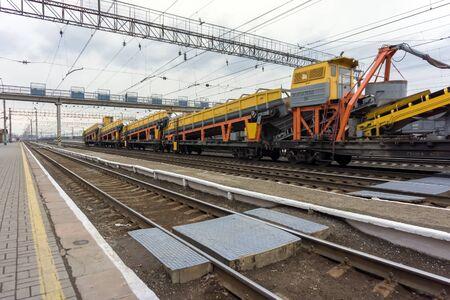 Tren de mercancías con equipos industriales se encuentra en las vías de una estación de tren de cruce con rieles en primer plano. Foto de archivo