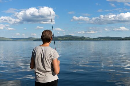 A woman fisherman stands with a fishing rod and catches fish against a blue lake and sky with clouds. Bright shot.