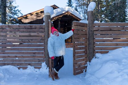An elderly woman stands near the gate near a wooden house among the snowdrifts in the forest.