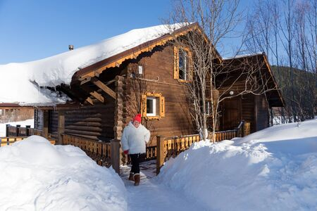 An elderly woman stands near the entrance to a wooden house, amid snowdrifts on a sunny winter day. Stock Photo