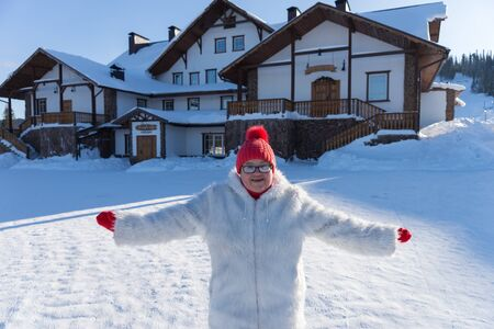 An elderly smiling woman stands with arms outstretched in front of the cottage, on a sunny winter day.