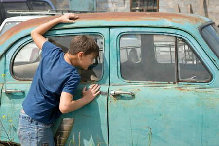 A boy, 11 years old, looks out the window of a rusty car in a dump of abandoned old cars on a sunny summer day.