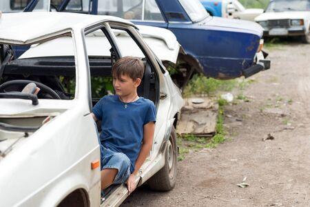Un niño de 11 años se sienta en un automóvil desmontado en un vertedero de autos viejos abandonados en un día soleado de verano.
