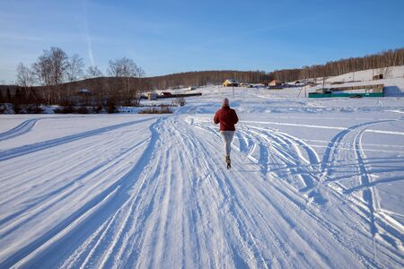 Girl runs along a winter road on a frozen lake towards a village on a hill, on a winter sunny day.