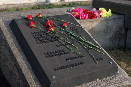 Red carnations lie on a tombstone with the names of fallen soldiers in the Victory Memorial