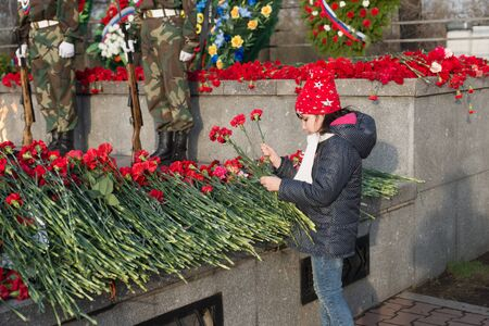The girl lays red carnation flowers on the Victory Memorial during the celebration of Victory Day. Krasnoyarsk Russia.