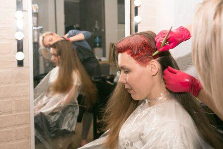 Une coiffeuse peint les cheveux d'une fille avec un pinceau, devant un miroir dans le salon du coiffeur.