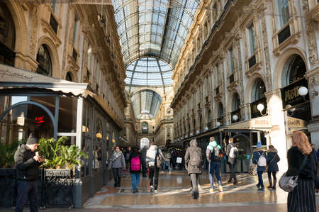 People walk through the Vittorio Emanuele II Gallery - a unique indoor shopping gallery in the center of Milan, built in 1865-1877. Italy.