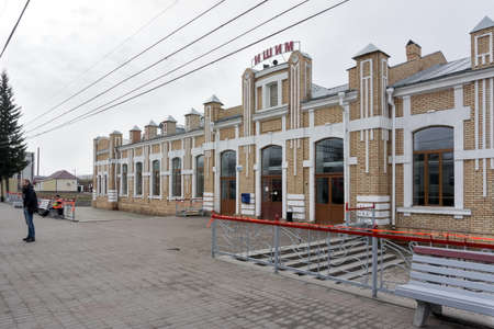 A man stands on the platform of the railway station (built 1913) in Ishim, on a cloudy spring day. Tyumen region. Russia. 報道画像