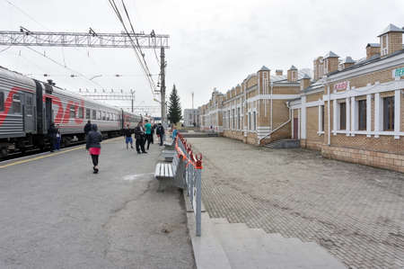 Passengers walk on the platform of the Ishim train station while the train was parking on a cloudy spring day. Tyumen region. Russia. 報道画像