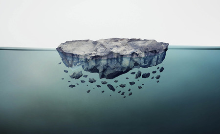 gravitation: Crumbling rock floating in clar blue water Stock Photo