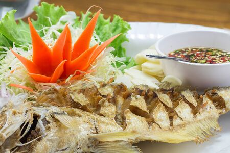 dish disk: grilled fish in white plate on wooden table Stock Photo
