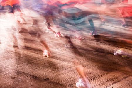 Runners running in city marathon, motion blur on sporty legs