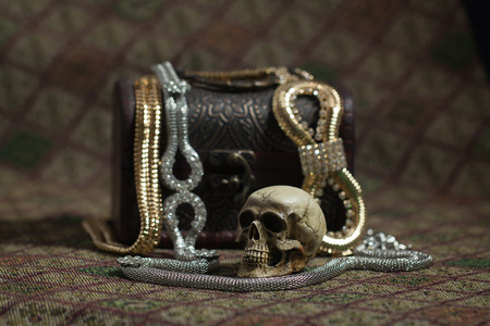 Still Life skull and small box with treasures on a fabric background photo