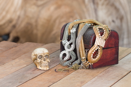 Still Life skull and small box with treasures on wooden  background photo