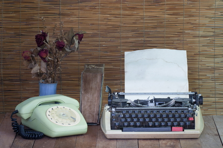 Still life with old typewriter telephone book with dry rose flowers on wooden table