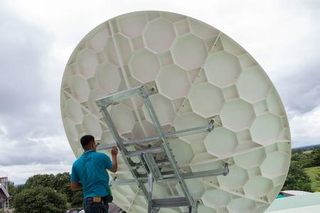 hombre pintando: hombre pintando de color bronz en el disco satélite