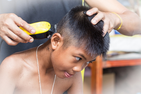 overexposed: little boy getting his head shaved by farther Stock Photo