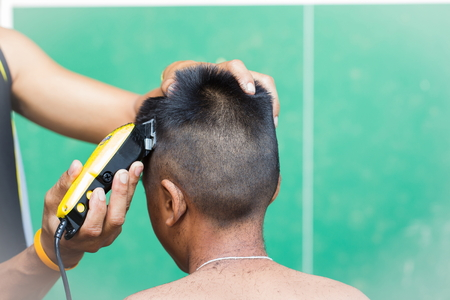 farther: little boy getting his head shaved by farther Stock Photo