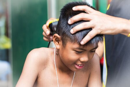 little boy getting his head shaved by farther Stock Photo