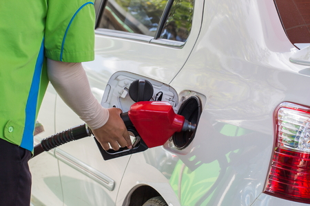 refilling: Worker refilling the white car with fuel