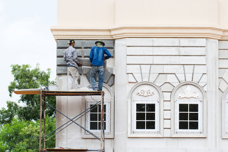 stucco facade: Two builders worker installing stucco decoration with float and plaste at outdoor wall over windows on facade of business building