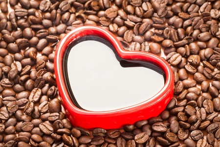 coffeetree: Coffee beans in red heart on wood background
