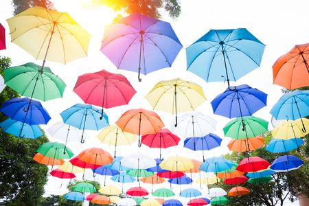 カラフルな傘の背景をぶら下がっています。空にカラフルなパラソル。ストリート装飾。 写真素材