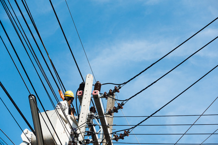 electricians repairing wire of the power line on electric power pole on crane. Reklamní fotografie