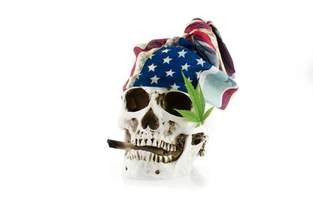 Still life of human skull, cannabis leaf and flag on white background