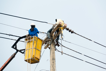Electrical utility workers repairing problem with power line on the help of truck crane 写真素材
