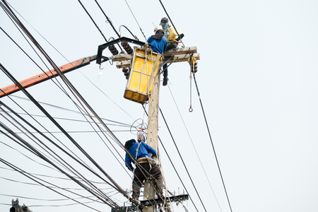 Electrical utility workers repairing problem with power line on the help of truck crane Stock Photo