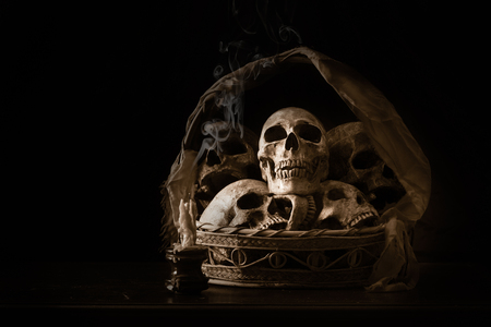 Human skulls in basket and candle, Still life image