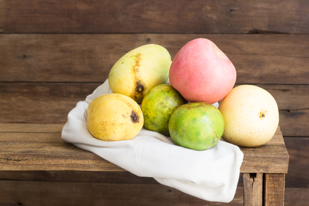 still life photography with apple, oranges and mango on wood 写真素材
