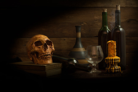 still life photography, human skulls, book, wine, wine glass  and candle on black table against art dark background  with window light 写真素材