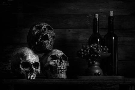 still life photography, human skulls, book, wine and grap on black table against art dark background  with window light 写真素材