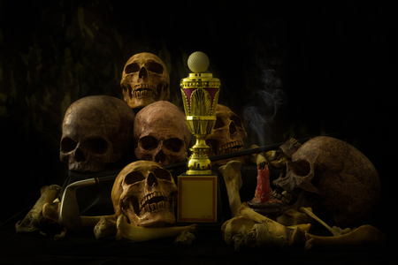 still life photography : golf ball on trophy, human skulls and candle on black table against art dark background with window light at left