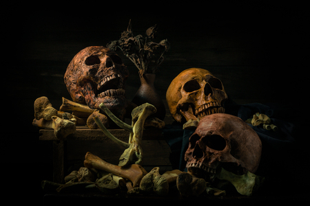 still life photography : human skulls, and candle on black table against art dark background with window light