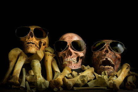 Awesome pile of skull human wear glasses and bone on black cloth background, Star Sing a song. Still Life style, selective focus, 写真素材