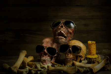 Awesome pile of skull human wear glasses and bone on wood background, Star Sing a song. Still Life style, selective focus,