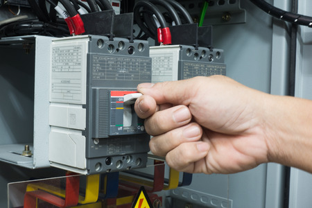 Hand of Engineer turning on switch in the electrical cabinet at control room 写真素材