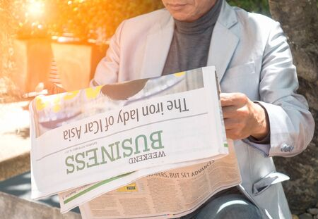 business, press, news  and concept - close up of businessman reading newspaper under tree