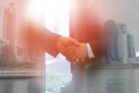 Teamwork concept. Close up of handshake on abstract city background. Double exposure.