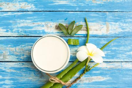 スパ新鮮なアロエベラ、ミルクとウッドの背景の花