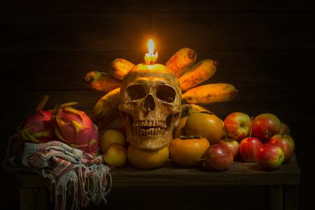 頭蓋骨、リンゴ、バナナ、ドラゴン フルーツ、柿、布や木製のテーブルにキャンドルのある静物 写真素材 - 88125633
