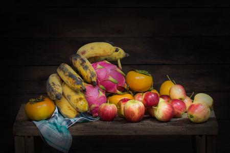 木のテーブルの上の頭蓋骨、リンゴ、バナナ、ドラゴンフルーツ、柿、布やキャンドルの静物